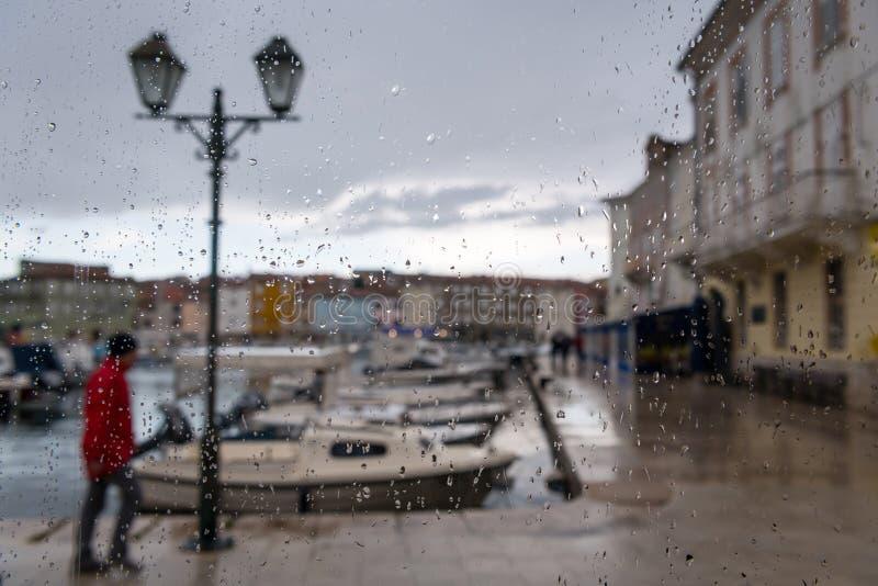 茨雷斯岛港口在一个雨天从与雨珠的一个窗口的后面 免版税库存照片