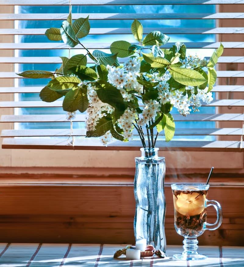 茶与emon的在木背景的和樱桃 窗口 免版税库存照片