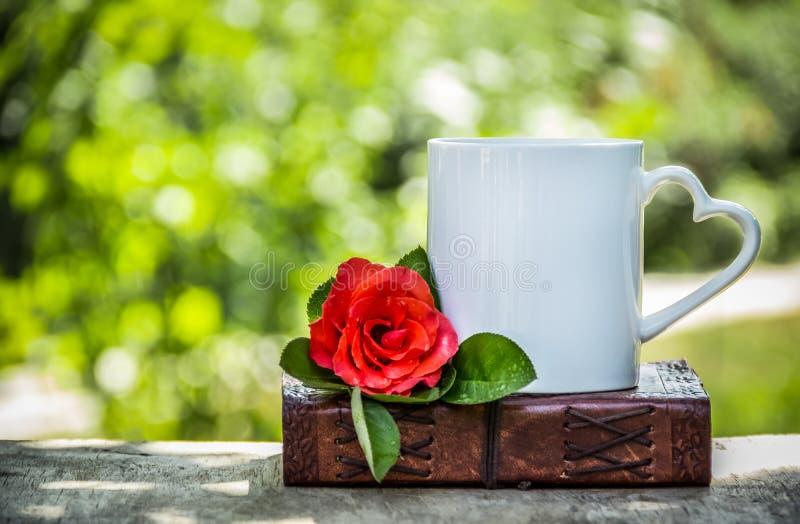 茶和一朵红色玫瑰 咖啡在庭院里 浪漫有心脏的早餐白色杯子 免版税图库摄影