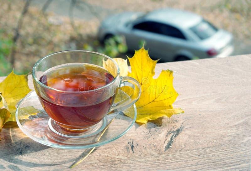 茶和在一张木桌上的黄色叶子 杯用在木桌上的热的茶在秋天背景 秋天背景特写镜头上色常春藤叶子橙红 免版税库存图片