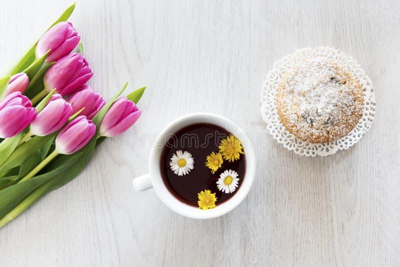 茶和松饼与绿色烘烤的杯子有郁金香的 免版税库存照片