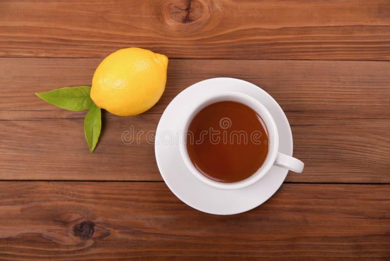 茶和柠檬与叶子在木背景 免版税库存图片
