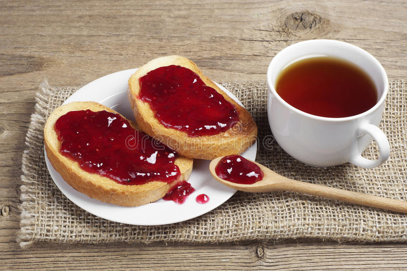 茶和白面包用草莓酱 库存图片