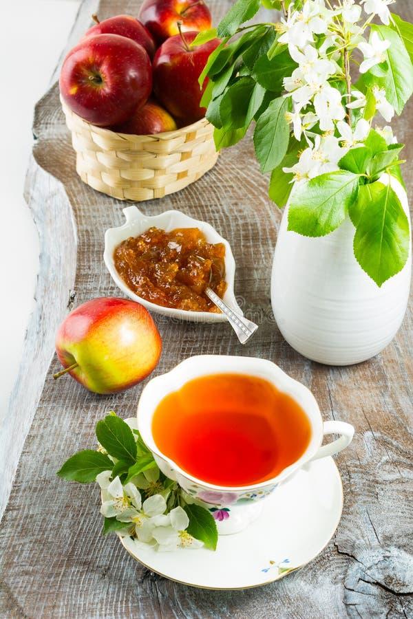 茶和苹果在土气木桌上阻塞 库存照片