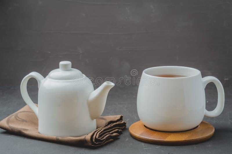 ? 茶和茶壶 在一张黑石桌上的白色商品 r 库存照片