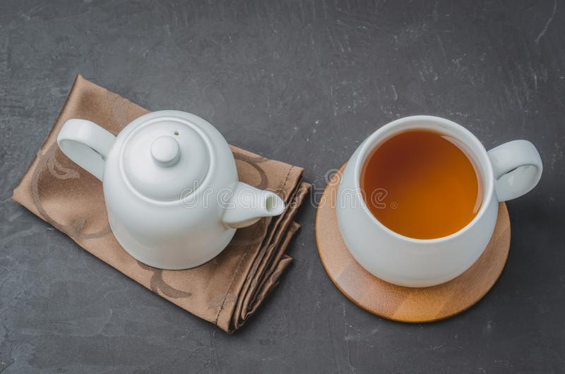 ? 茶和茶壶 在一张黑石桌上的白色商品 r 库存图片