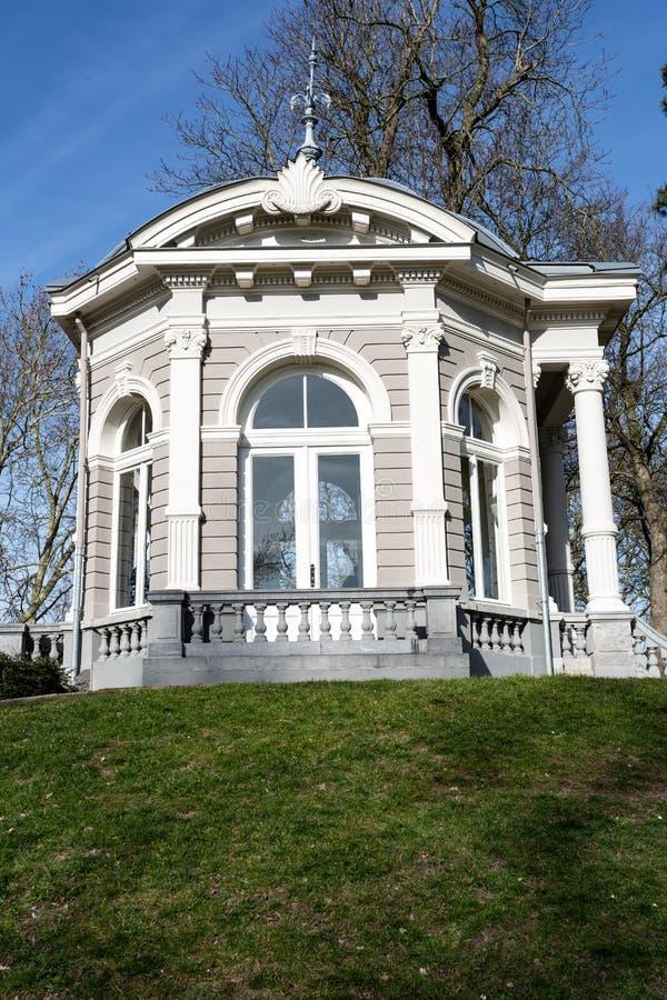 茶圆顶或Gloriette与它的被成拱形的窗口与柱子和石栏杆在小山 免版税库存照片