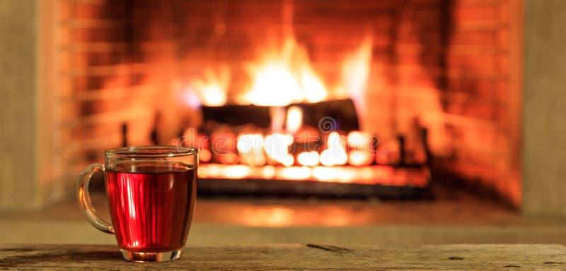 茶在灼烧的壁炉背景的 免版税库存照片
