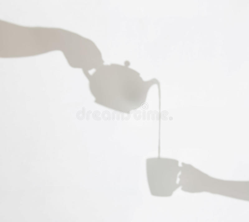 茶壶倾吐的液体的精美阴影到杯子里由fem举行了 图库摄影