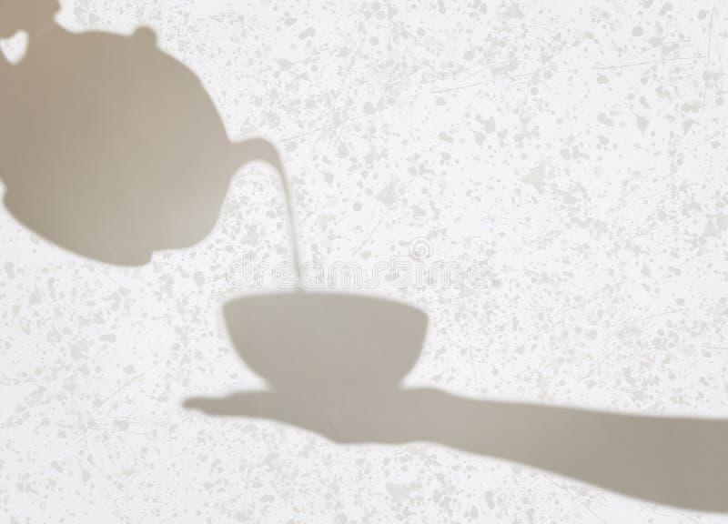 茶壶倾吐的液体的精美阴影到杯子里由fem举行了 免版税库存图片