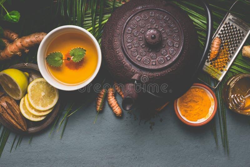 茶壶和健康姜黄香料茶用柠檬、姜和蜂蜜在黑暗的背景,顶视图 免疫促进的补救 免版税库存图片