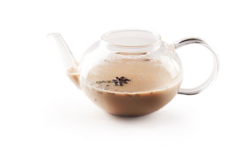 茶壶透明茶壶用在白色背景隔绝的印度全国masala茶 牛奶,姜,豆蔻果实,丁香,肉豆蔻,st 免版税库存照片