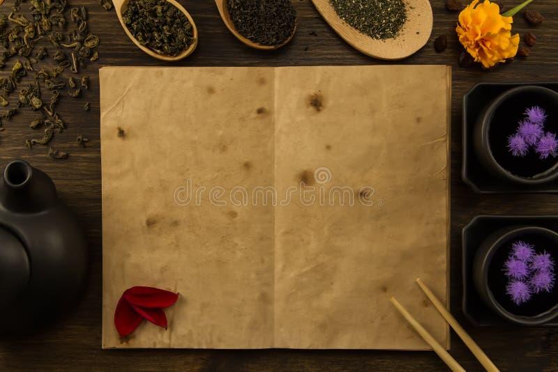 黑茶壶,两个杯子,茶汇集,花,老在木背景的空白开放书 库存照片