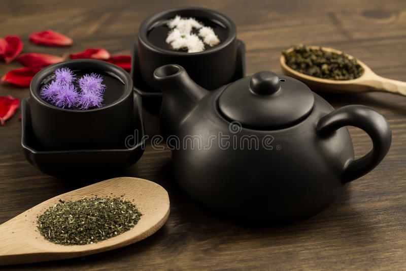 黑茶壶,两个杯子,茶汇集,花 库存图片
