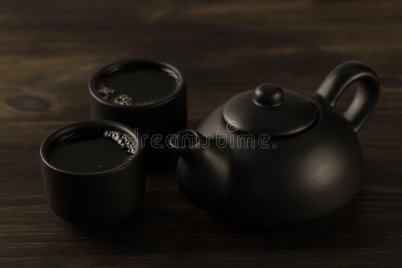 黑茶壶,在老木背景的两个杯子 免版税库存图片