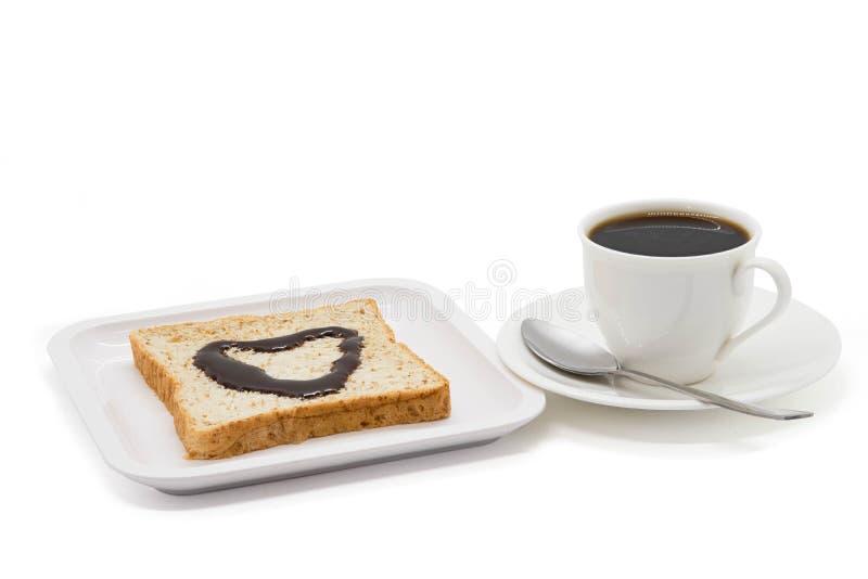 茶或咖啡用匙子和巧克力面包在板材 库存照片