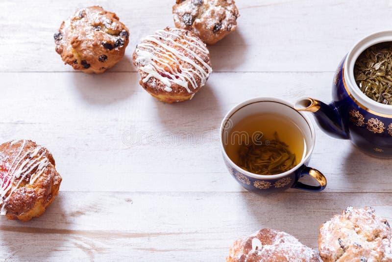 茶杯、茶壶和松饼在白色木桌上,设置了茶壶并且酿造了茶与蛋糕在桌,绿色黑草本热的饮料上 库存图片