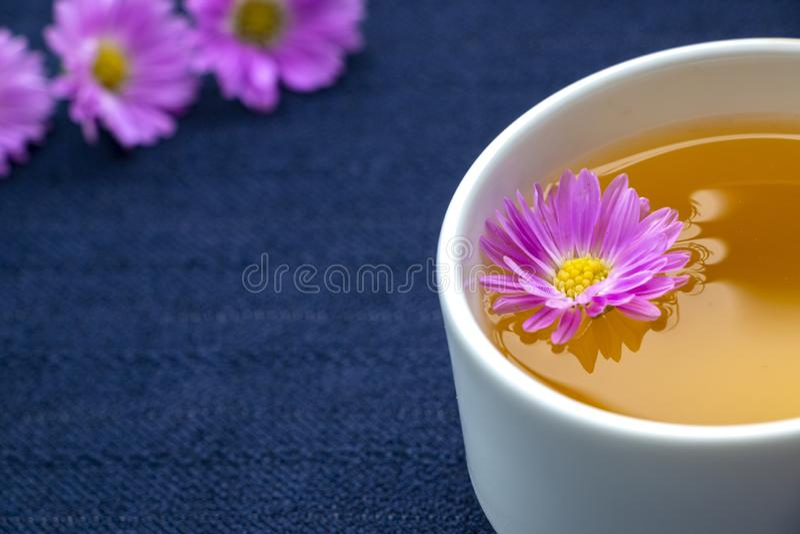茶杯和紫罗兰色花在深蓝桌布背景 免版税库存照片