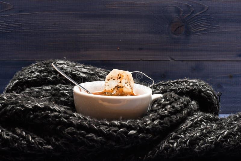 茶杯和被浸洗的袋子茶包裹与被编织的围巾 秋天饮料概念 酿造在杯子的茶的过程 杯子 免版税库存图片