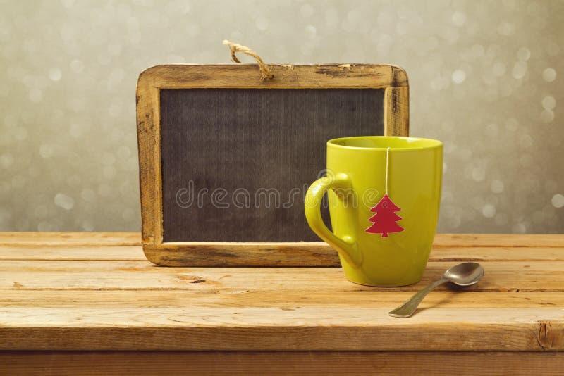 茶杯和黑板在木桌上 抽象空白背景圣诞节黑暗的装饰设计模式红色的星形 免版税图库摄影