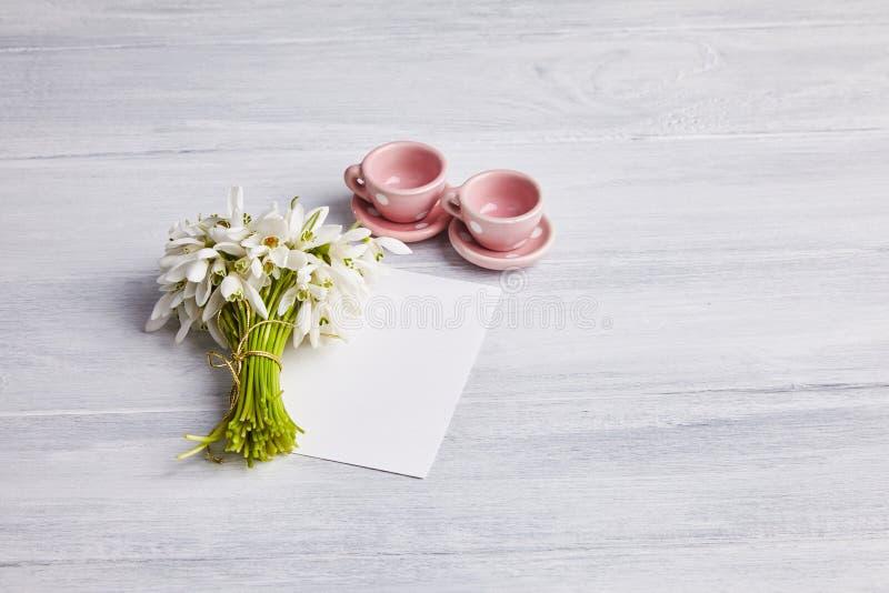 茶杯和snowdrops花束在白色生锈的木桌上 免版税图库摄影