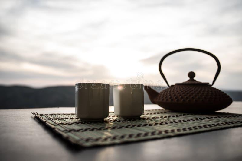 茶概念 日本茶道文化东部饮料 茶壶和杯子在桌上与竹叶子在日落 免版税库存图片
