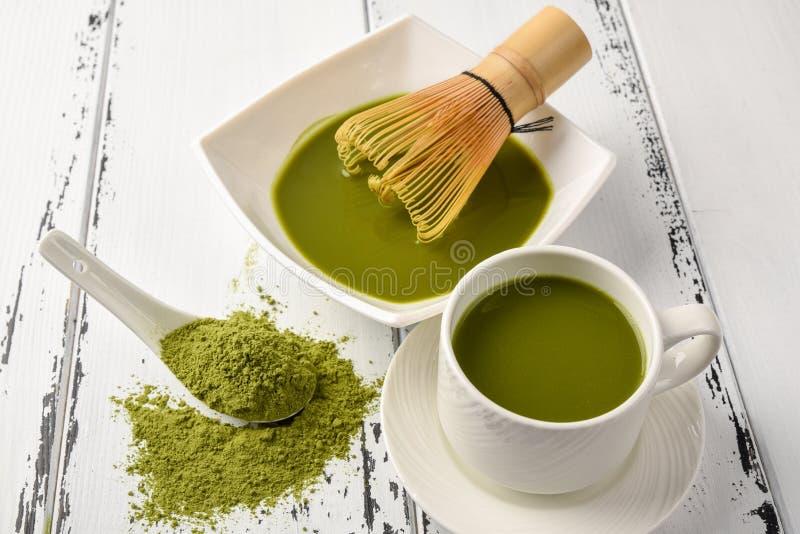 茶比赛的准备:滚保龄球与扫和茶杯,绿茶在一把白色陶瓷匙子的比赛粉末 免版税库存图片