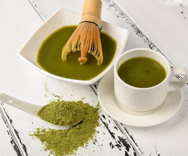茶比赛的准备:滚保龄球与扫和茶杯,绿茶 免版税库存图片