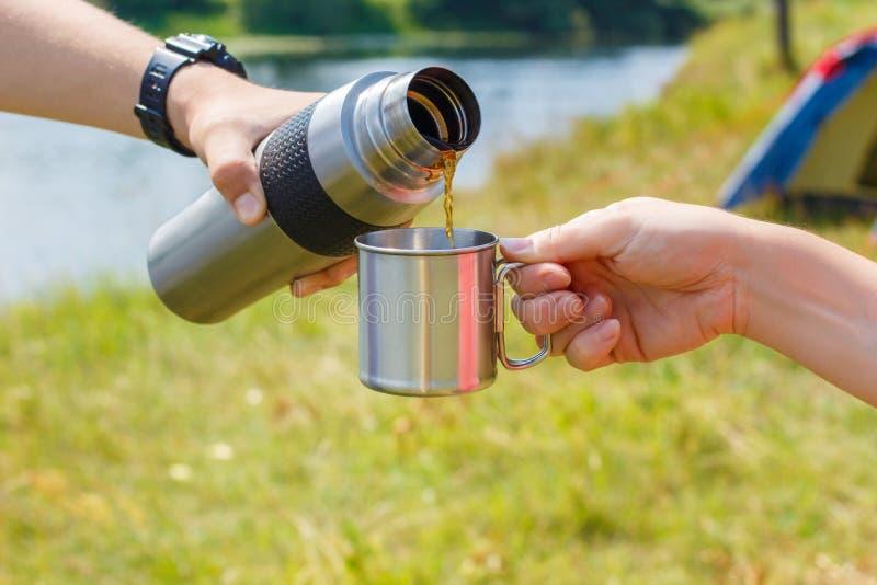 茶涌入了从热水瓶的一杯 免版税库存照片