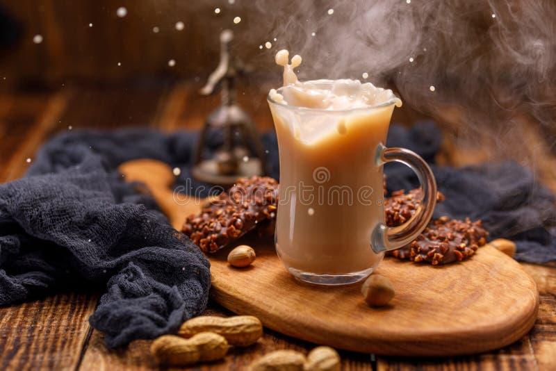 茶用在一个玻璃杯子的饼干有飞溅的 抽烟,奶茶和与坚果的巧克力饼干早餐溢出 免版税库存照片