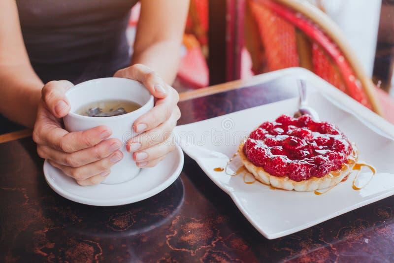 茶用在咖啡馆,关闭的甜蛋糕点心手 免版税库存照片