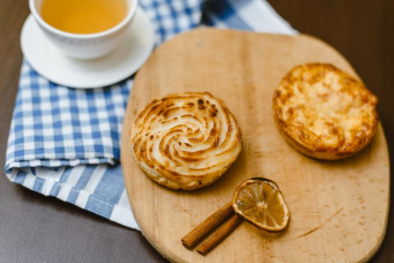 茶用在木背景的酸奶干酪小圆面包 可口早餐 库存图片