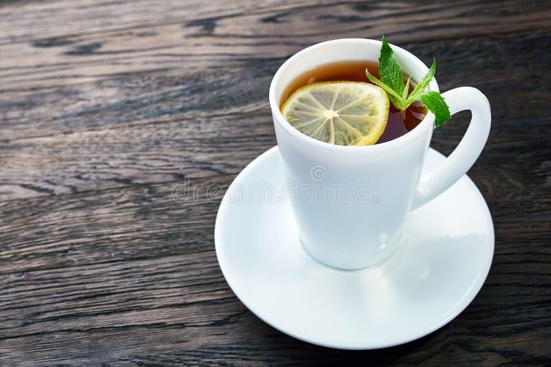 茶用在白色杯子,肉桂条的柠檬,编织了在木桌上的羊毛围巾 库存照片