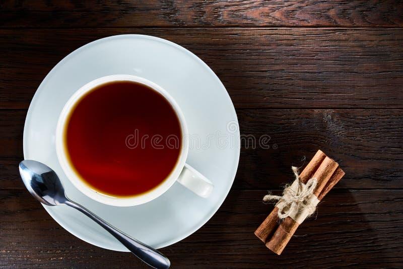茶用在白色杯子,肉桂条的柠檬,编织了在木桌上的羊毛围巾 免版税库存图片