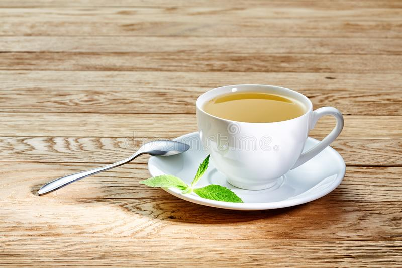 茶用在白色杯子,肉桂条的柠檬,编织了在木桌上的羊毛围巾 免版税库存照片