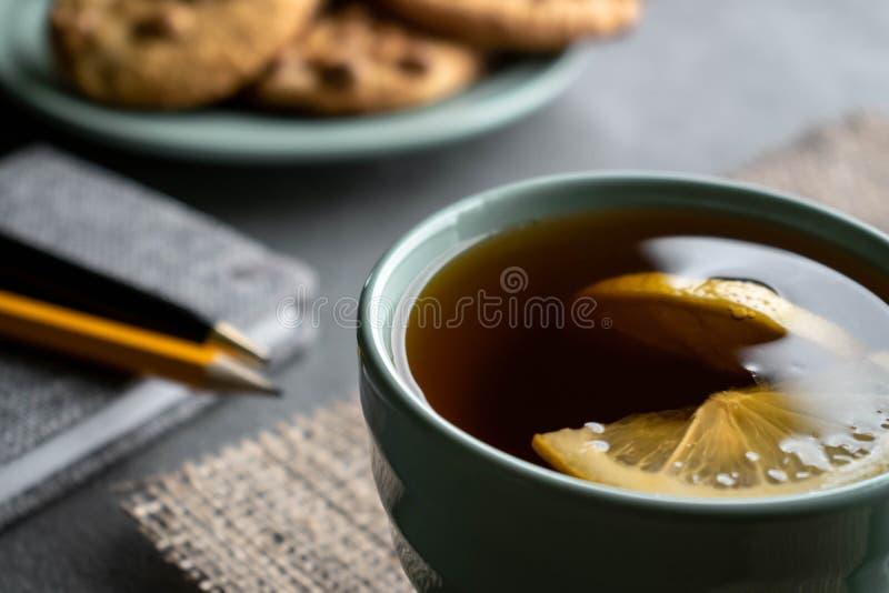 茶用柠檬、花生曲奇饼和灰色笔记本有笔和铅笔的 库存图片