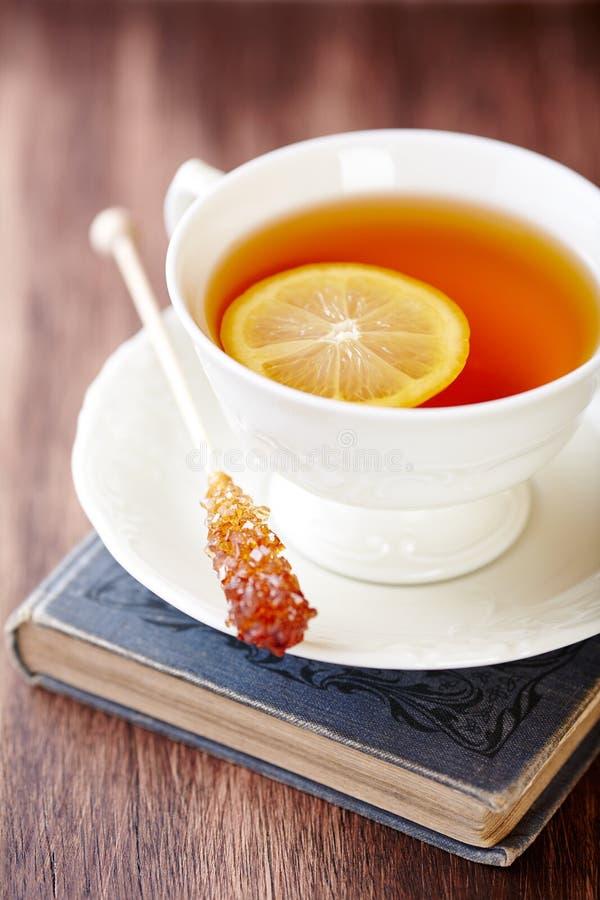 茶用柠檬和红糖在一本旧书黏附 图库摄影