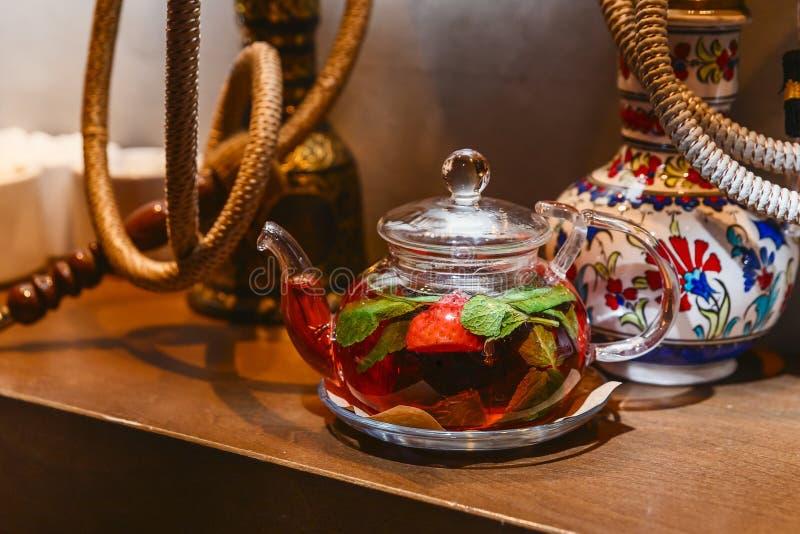 茶用薄菏和草莓在一个透明茶壶 库存图片