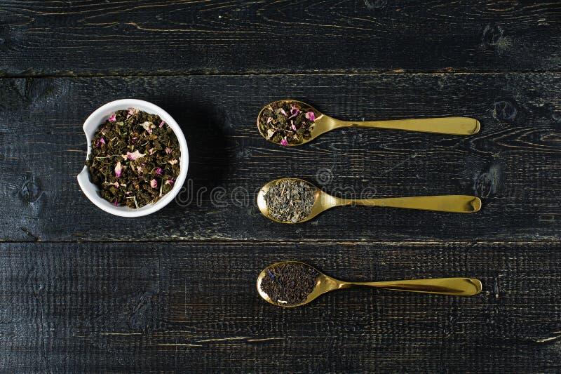 茶的三种类型在绿色的匙子-,黑色和Rooibos的 库存照片