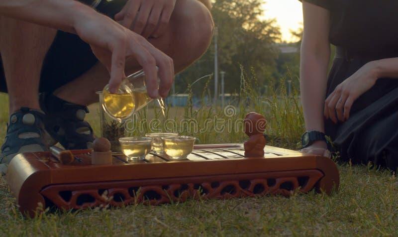 茶道在公园 在杯子的人倾吐的茶 免版税库存图片
