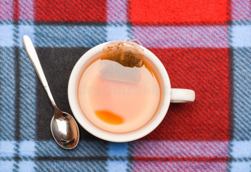 茶酿造概念 杯子用开水、茶袋和匙子填装了在五颜六色的格子花呢披肩背景 茶酿造的过程 免版税库存图片
