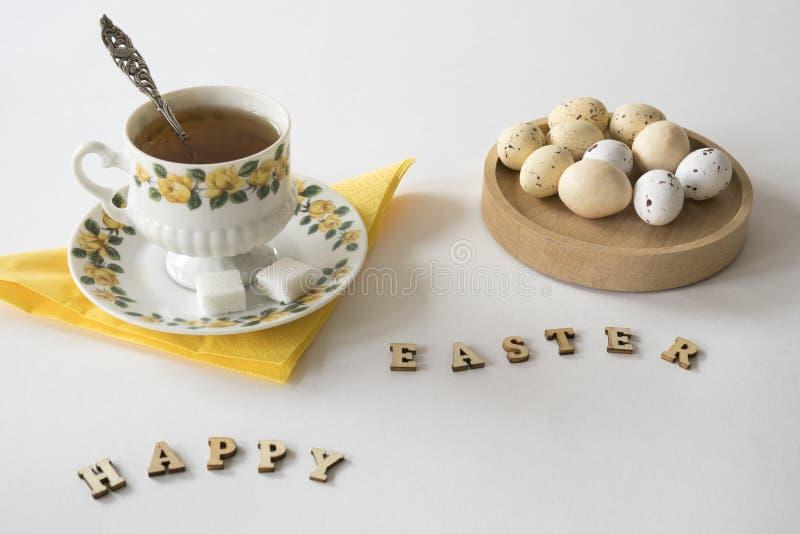 茶,白色和黄色复活节彩蛋,木信件,反对白色桌 库存图片