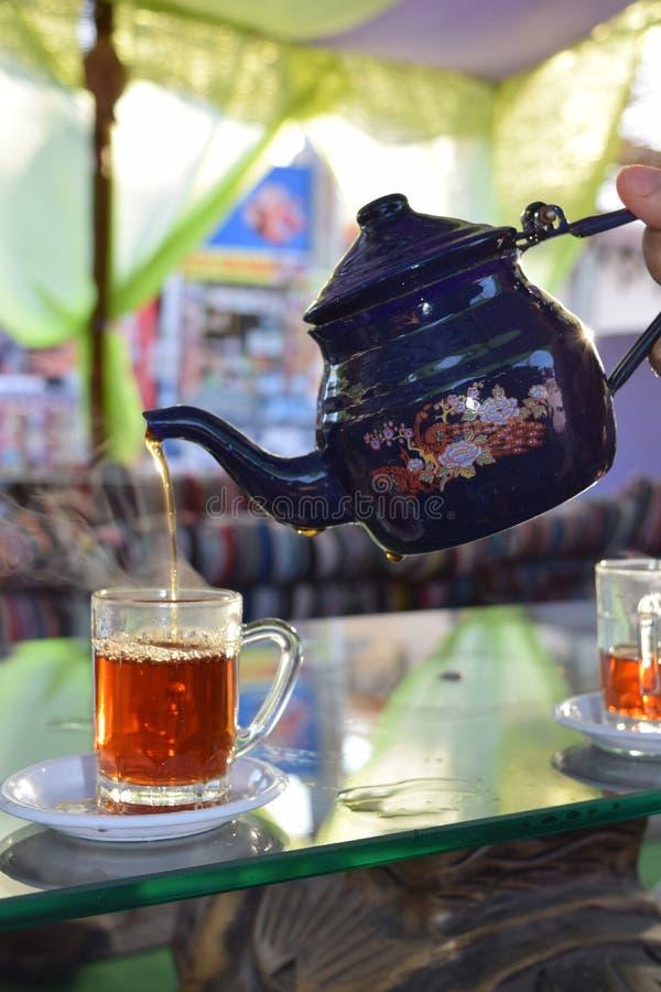 茶从茶壶倾吐了入一个玻璃杯子 免版税库存图片