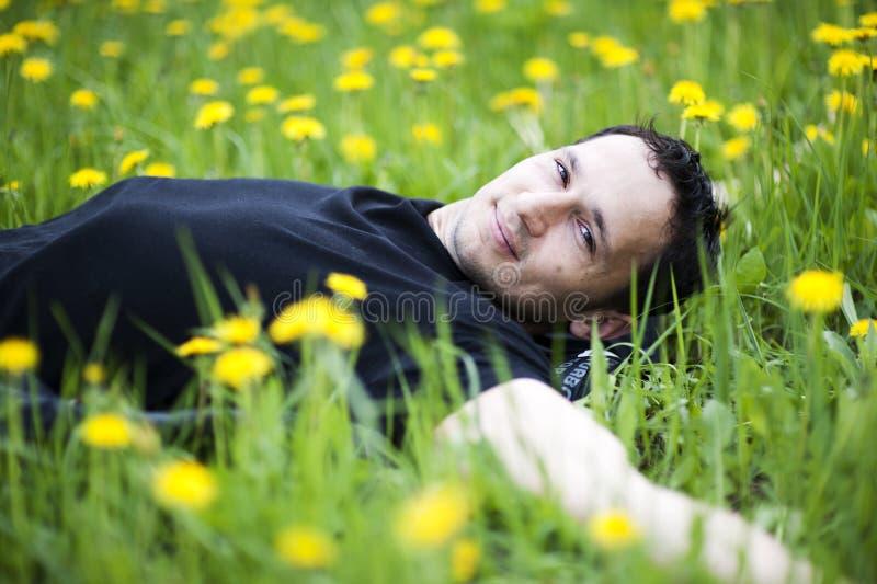草位于的人年轻人 免版税库存照片