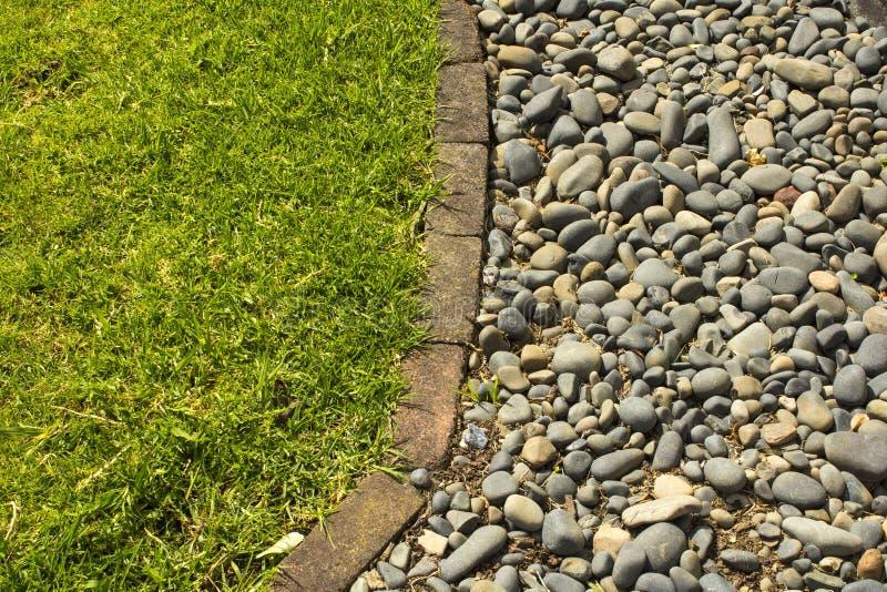 绿草和小卵石背景 免版税库存图片