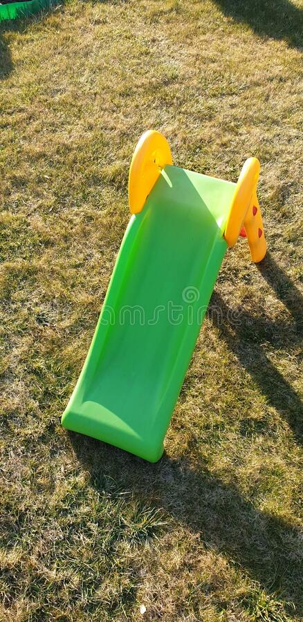 草地上的绿色塑料滑梯 库存照片