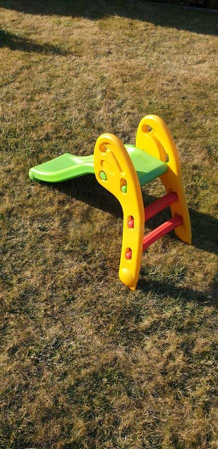 草地上的绿色塑料滑梯 免版税库存图片