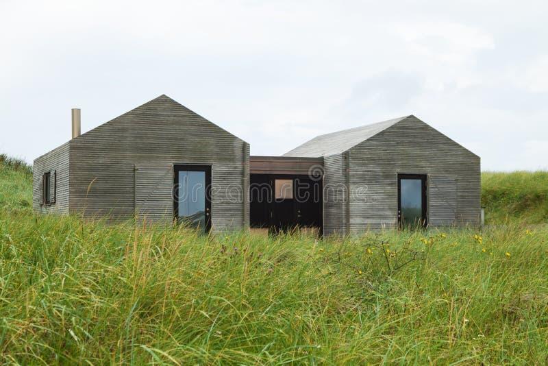 草坪包围的现代木房子 免版税库存图片
