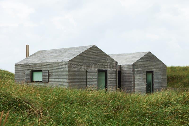 草坪包围的现代木房子 图库摄影