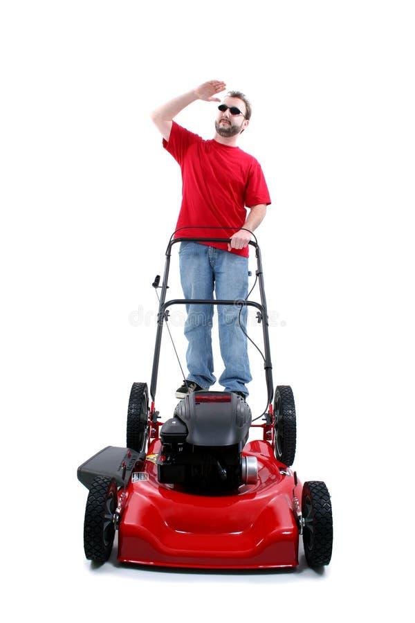 草坪在红色白色的人刈草机 免版税库存照片
